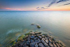 Golfbreker bij zonsondergang in IJsselmeer van