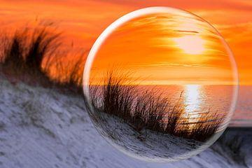 Glaskugel mit orange Sonnenuntergang am Ufer mit Meer Dünen und Strand von Ben Schonewille