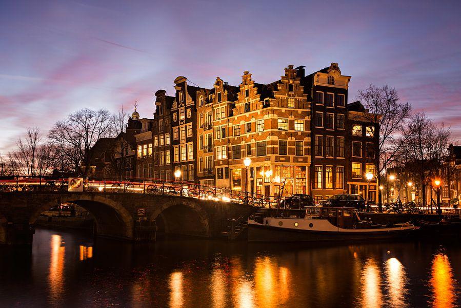 Amsterdams stadszicht met grachtenpanden in de avond