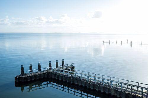 Hollands waterlandschap met reflectie, een steiger en wolken