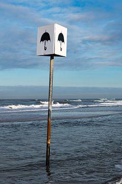 Schild mit dem Bild eines Sonnenschirms am Strand von Petten von Wim Stolwerk