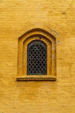 Vitrail d'église dans un mur ocre. sur Axel Weidner