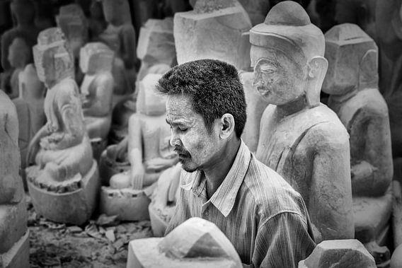 Beeldhouwer aan het werk zittend tussen Budha beelden in Mandelay aan de Marble Road van Wout Kok