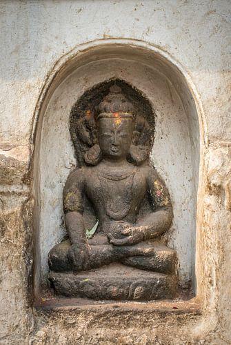 Boeddha beeld in een nis van een witte muur van een tempel in Nepal
