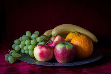 Stilleven van fruitschaal met vers fruit op warm rode achtergrond van Piertje Kruithof
