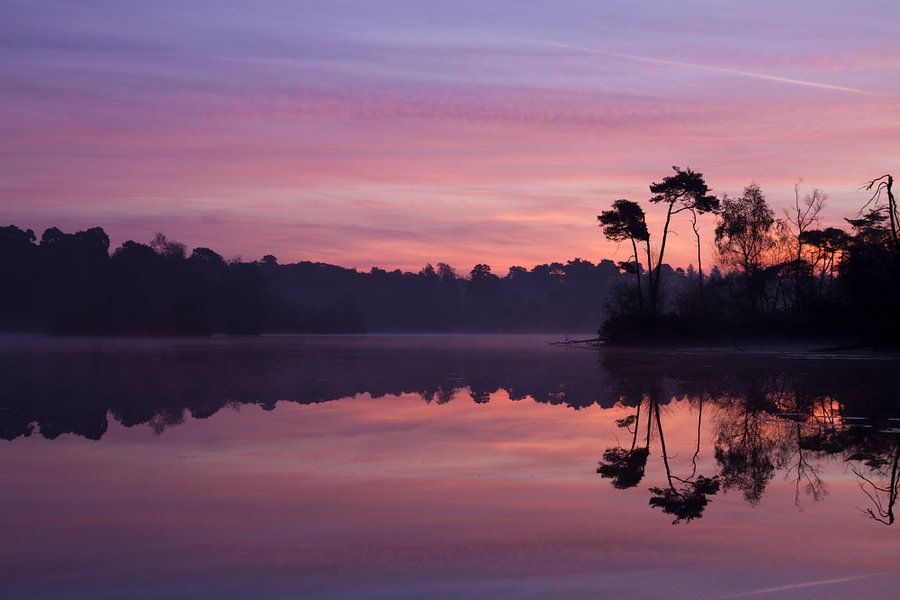 De lucht kleurt mooi op door de zonsopkomst aan het meer
