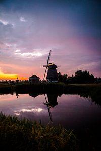 Zonsondergang op een dijkje in west friesland met een molen op de achtergrond van Lindy Schenk-Smit