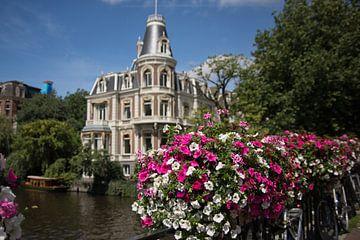 Amsterdam-Szene mit Blumen im Vordergrund auf dem Geländer einer Brücke von Gea Gaetani d'Aragona