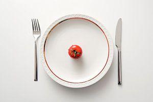 Tomate fraîche dans une assiette avec un bord doré et des couverts sur fond blanc, régime avec des l
