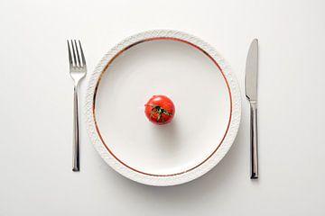 Tomate fraîche dans une assiette avec un bord doré et des couverts sur fond blanc, régime avec des l sur Maren Winter