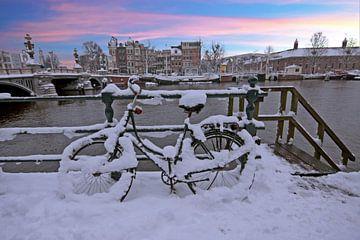 Besneeuwd Amsterdam in de winter bij zonsondergang van Nisangha Masselink