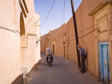 Motorrijder en oude man de straten van Yazd, Iran van Teun Janssen