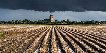 Donkere lucht boven het kerkje van Ferwerd, Friesland. van