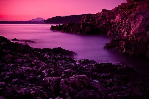 Rotsachtige baai na zonsondergang van