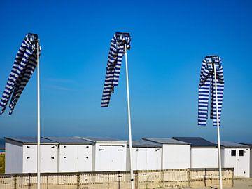 Witte strandhuisjes en vlaggenmasten van