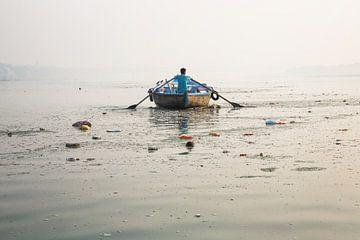 Een man met een houten boot roeit over de heilige Ganges rivier in Gosaba, West-Bengalen, India van Tjeerd Kruse