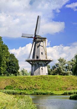 Moulin à vent hollandais sur une digue avec le ciel bleu et les nuages sur Tony Vingerhoets