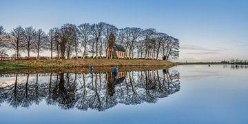 De Terp en het kerkje van Hijum, Friesland, gespiegeld in de ijsbaan van Harrie Muis