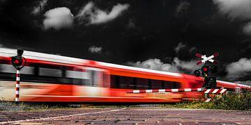 Zug fährt an einem Hochgeschwindigkeits-Bahnkreuz bei Deinum vorbei von Harrie Muis