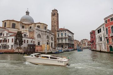 Alte Gebäude, Kirche und weißes Schnellboot auf Kanal in der Altstadt von Venedig, Italien von Joost Adriaanse