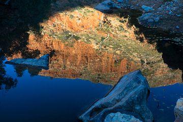 Rode klif reflecteert in de waterhole van