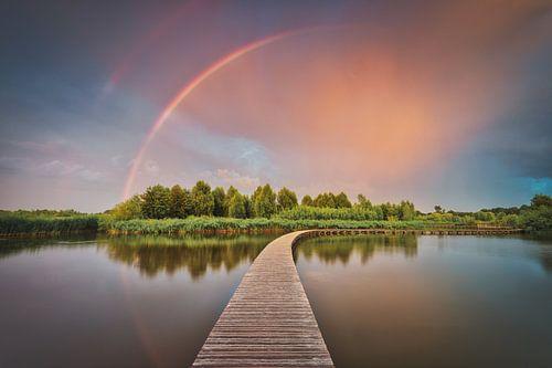 Dreigende wolken en regenboog boven Nederlands landschap