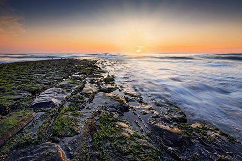zonsondergang achter een golfbreker in de Noordzee
