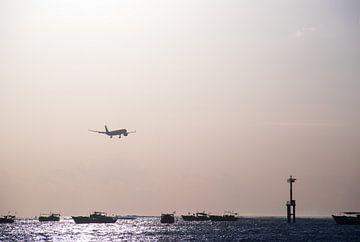 Landend vliegtuig boven zee tijdens zonsondergang von Chantal Schutte