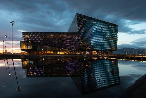 Harpa met zijn reflectie in de haven van Reykjavik van