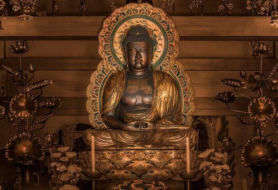 Gouden standbeeld van de Japanse Boeddha Shakyamuni omgeven door lotusbloemen.