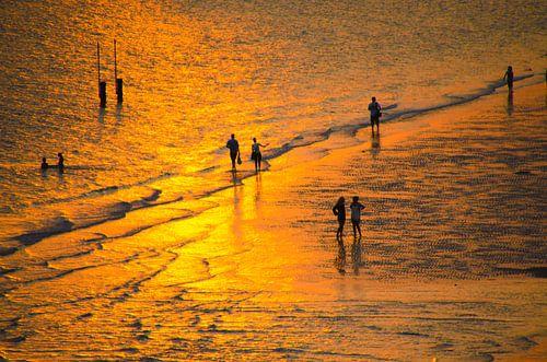 Een strandwandeling langs het strand tijdens een zonsondergang van