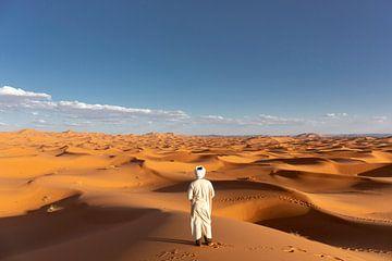 Afrikaanse man kijkt uit over de duinen van de Afrikaanse woestijn, de Sahara van Tjeerd Kruse