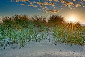 zicht op de duinen en de Noordzee tijdens de zonsondergang van