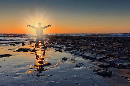 zonsondergang achter een jongen op het strand