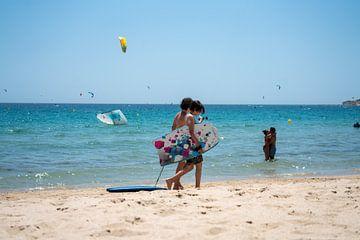 Bodysurfers (kinderen) lopend langs het strand van Tarifa. van Monique van Helden
