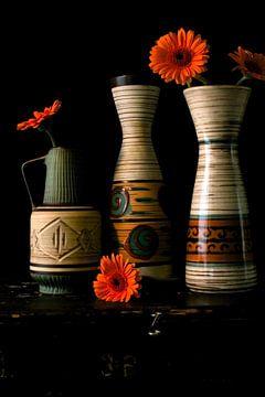 Foto van een stilleven met jaren 60 vazen en oranje gerbera's. van Therese Brals
