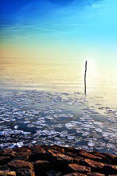 Zon gaat onder in kalm bevroren meer van Jan Brons