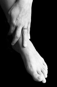 hand van een vrouw ligt op haar voet von Anita Hermans