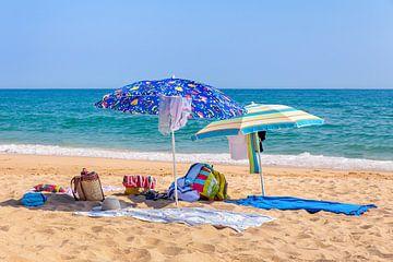 Zwei Sonnenschirme Handtücher Kleidung und Taschen am Strand von