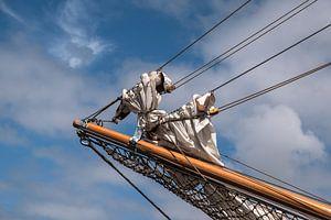 kluiverboom met gereefde zeilen op de boeg van een historisch zeilschip tegen een blauwe lucht met w