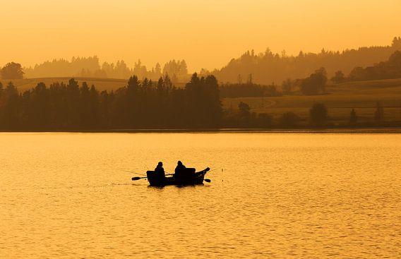 Twee vissers in een roeibootje op het meer bij zonsondergang