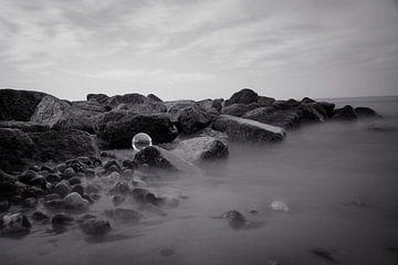 De glazen bol op de rotsen in de zee