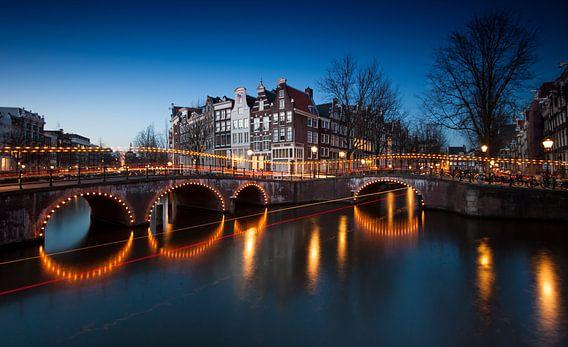Amsterdam bij ondergaande zon met zijn typische grachten, huizen en bruggen.