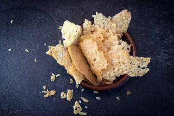 knapperige parmezaanse kaaschips, zelfgemaakte partysnack in een kom op een donkere leisteen achterg van Maren Winter