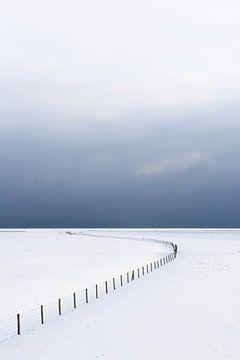 Eine leere, schneebedeckte Winterlandschaft im Nationalpark Lauwersmeer. Am Horizont treiben dunkle  von Bas Meelker