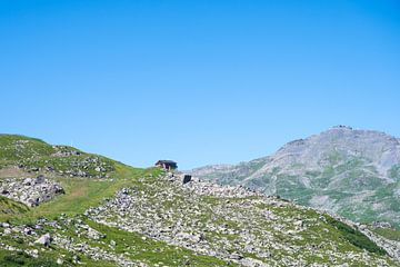 Ein einsames Haus auf einer Bergwiese in den französischen Alpen.