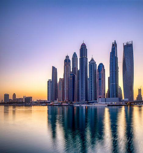 De zon komt op achter de skyline van Dubai van