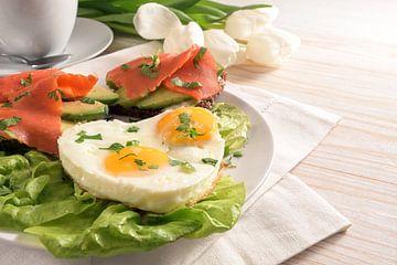 Urlaubsfrühstück mit Liebe, Spiegeleier in Herzform, Sandwiches mit Avocado und Räucherlachs auf Sal