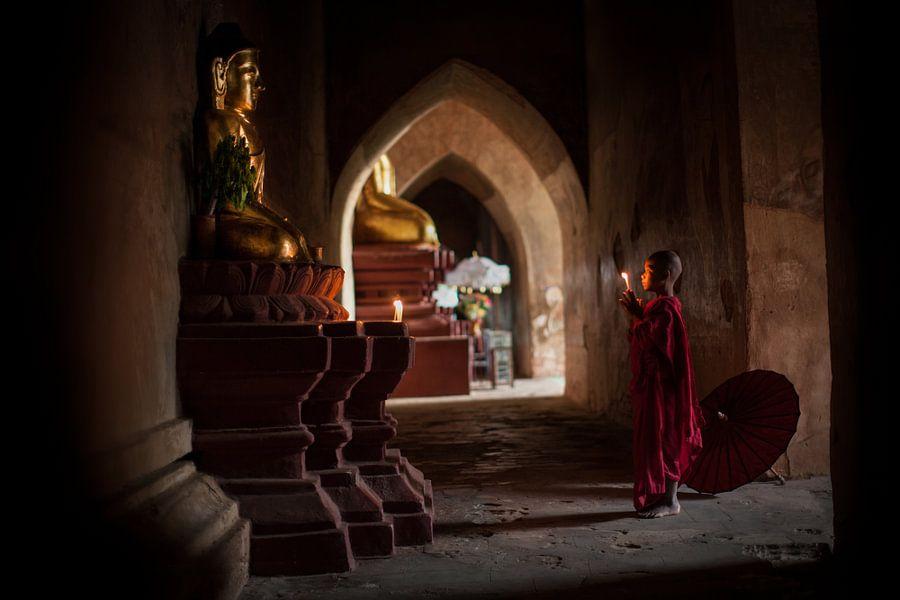 Jonge monnik in Bagan Myanmar bidt voor een beeld van Budha. Wout Kok One2expose Photography van Wout Kok