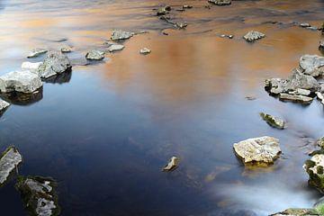 In het rustige water liggen grote stenen van Ulrike Leone